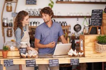 dia do comerciante - casal dono de loja conversando em torno de um balcão de loja