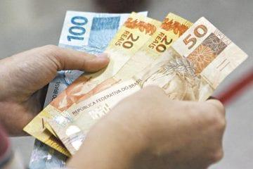 salário do trabalhador intermitente - mãos contando dinheiro