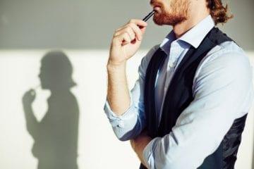 como calcular o salário intermitente - homem com uma caneta na boca pensativo