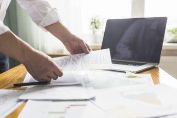contrato intermitente de trabalho - Mão do empresário segurando o documento sobre a mesa de madeira