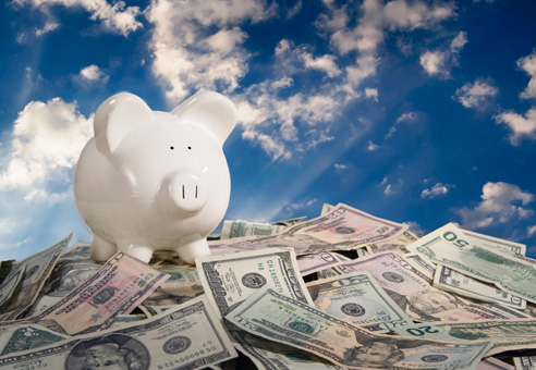 Como Economizar com o Trabalho Intermitente - cofrinho de porquinho sobre uma pilha de dinheiro