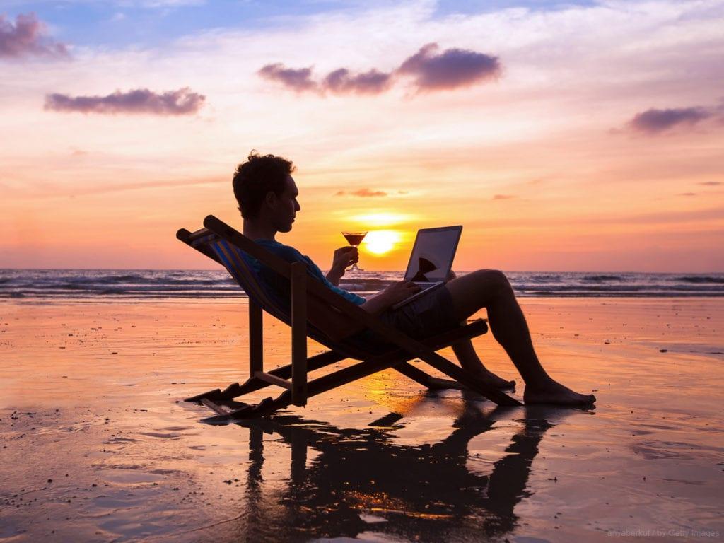 trabalho intermitente - homem na praia setando numa espreguiçadeira no fim de tarde tomando vinho e lendo