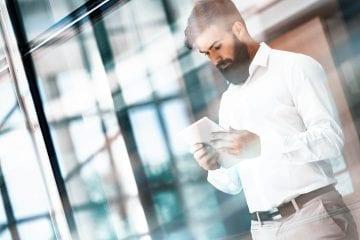 tecnologia pode ajudar na gestão dos funcionários - homem no escritório mexendo em um tablet