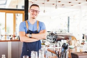 trabalho intermitente para pequenas e médias empresas - dono de cafeteria sorrindo no trabalhado com os braços cruzados