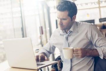 exemplos de trabalho intermitente - homem pensativo olhando pro computador