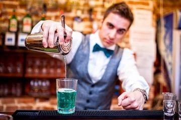 Regime de Trabalho Intermitente - barman serviço um drink sobre o balcão de madeira