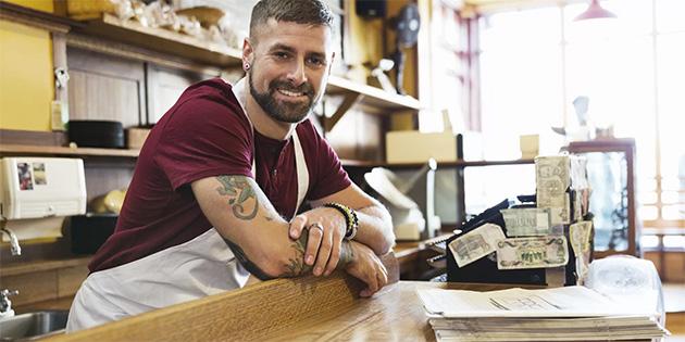 exempos de trabalho intermitente - homem sorrindo apoiado num balcão de loja