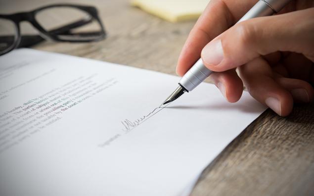 Trabalho intermitente e a reforma trabalhista - mão masculina que assina o contrato do empregado