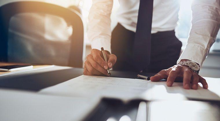 Benefícios do trabalho intermitente - homem de terno assinando um contrato