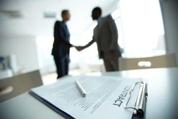 Duas pessoas apertando as mãos após assinarem o contrato